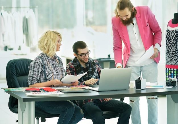 Designer moderno e sua equipe estão trabalhando em novos modelos no estúdio criativo de roupas
