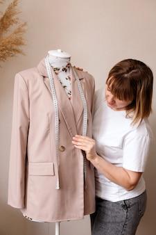 Designer perto da jaqueta no manequim