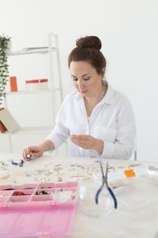 Designer profissional de acessórios fazendo joias feitas à mão em estúdio, oficina de criatividade e