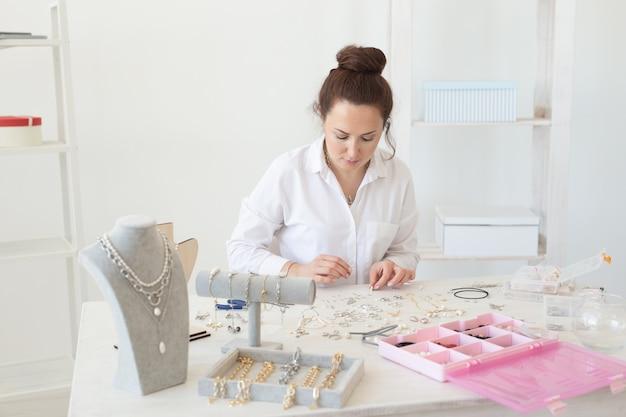 Designer profissional de acessórios fazendo joias feitas à mão em estúdio, oficina de moda, criatividade e