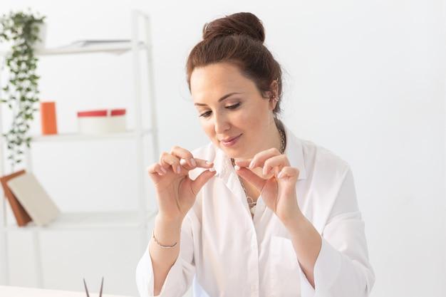 Designer profissional de acessórios fazendo joias feitas à mão em oficina de estúdio. moda, criatividade