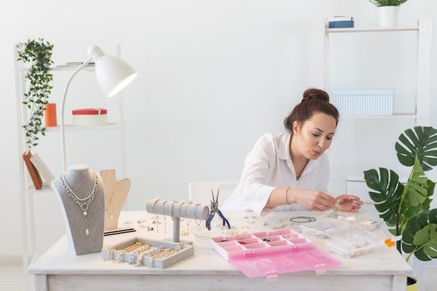 Designer profissional de acessórios fazendo joias feitas à mão em oficina. moda, criatividade e conceito artesanal.