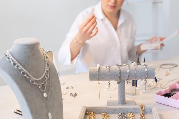 Designer profissional de acessórios que faz joias feitas à mão em estúdio, oficina de criatividade