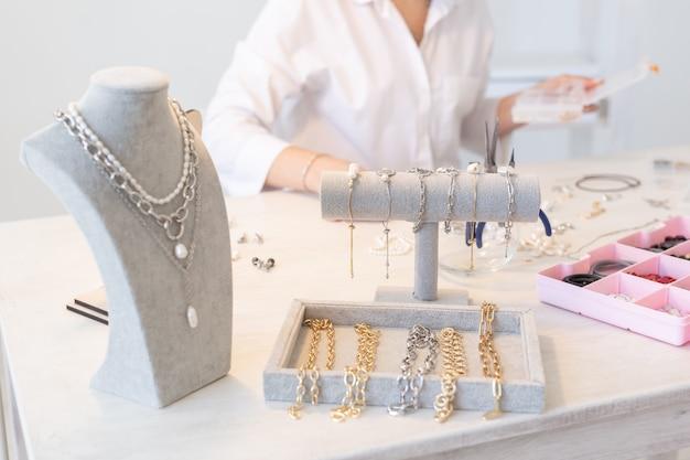 Designer profissional de acessórios que faz joias feitas à mão em estúdio, oficina de moda, criatividade e