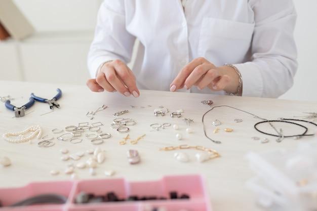 Designer profissional de joias fazendo joias feitas à mão em oficina de estúdio close-up. moda, criatividade e conceito artesanal