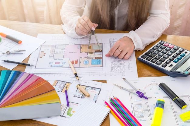 Designer trabalhando com bússola sobre a planta da casa