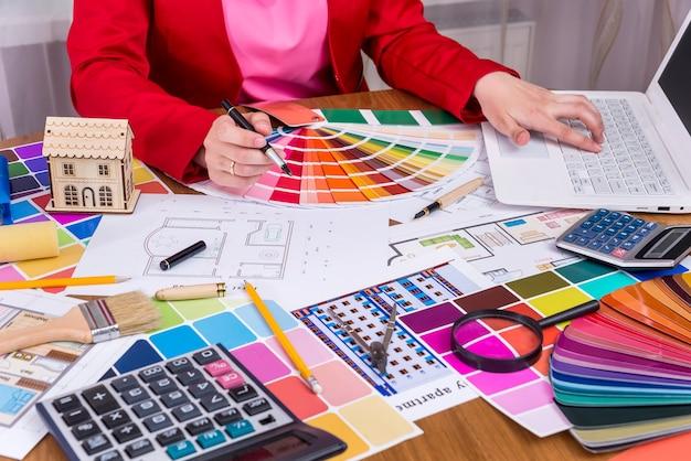 Designer trabalhando com paleta de cores e laptop