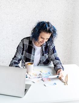 Designer trabalhando com paletas de cores e laptop em seu estúdio de arte