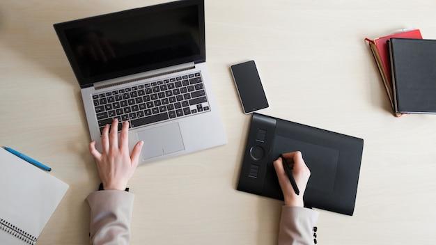 Designer trabalhando em laptop e tablet gráfico