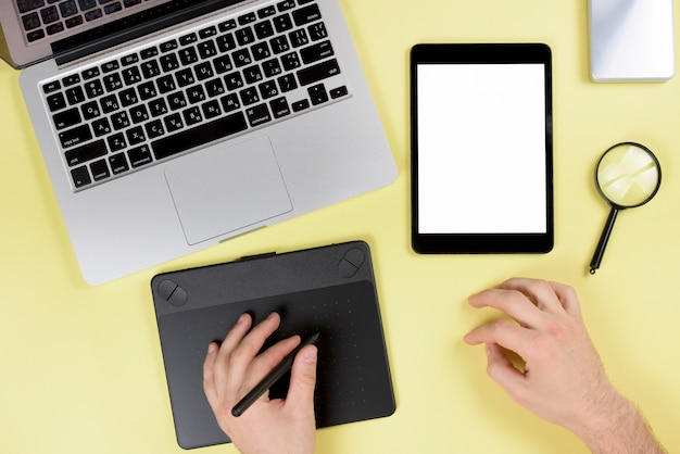 Designer trabalhando em tablet digital gráfico com caneta na mesa amarela