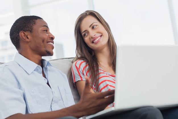 Designers criativos alegres que trabalham juntos em um laptop
