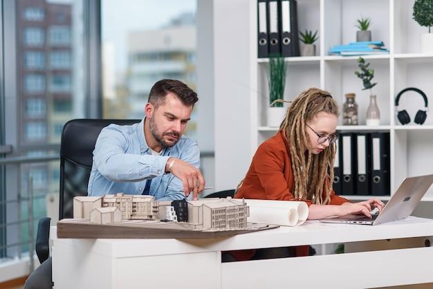 Designers criativos, masculinos e femininos, altamente qualificados, trabalhando com maquetes de futuros edifícios