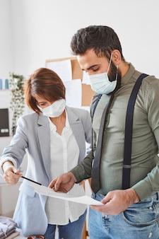 Designers de moda com máscaras médicas verificando planos de linha de roupas no ateliê