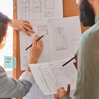 Designers de moda consultam planos para nova linha de roupas no quadro de ideias