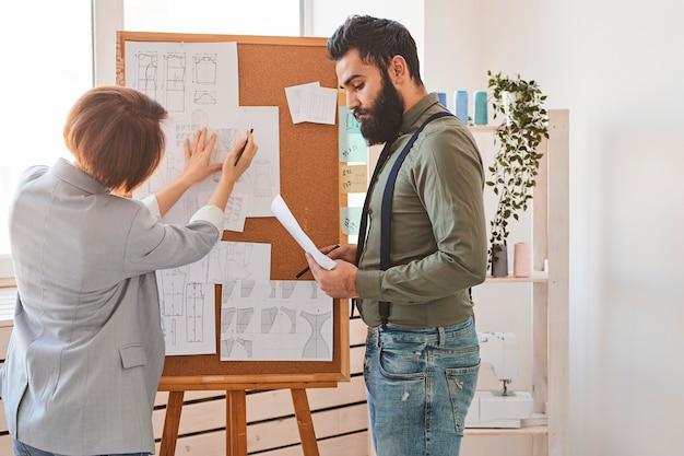 Designers de moda em ateliê consultando planos de linha de roupas no quadro de ideias