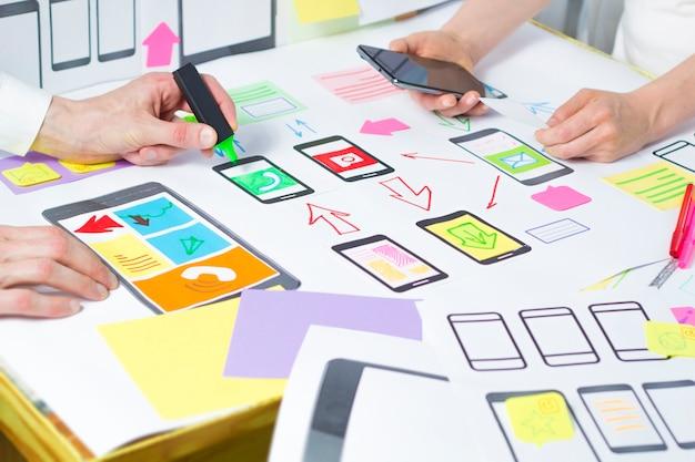 Designers desenvolvem e criam aplicativos móveis para telefones.