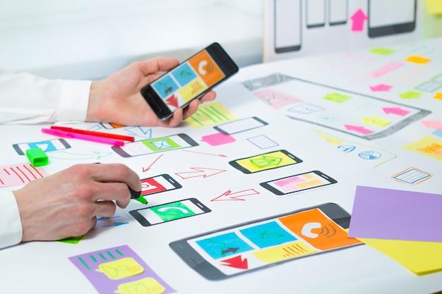 Designers desenvolvem e criam um projeto de aplicativos para telefones celulares.