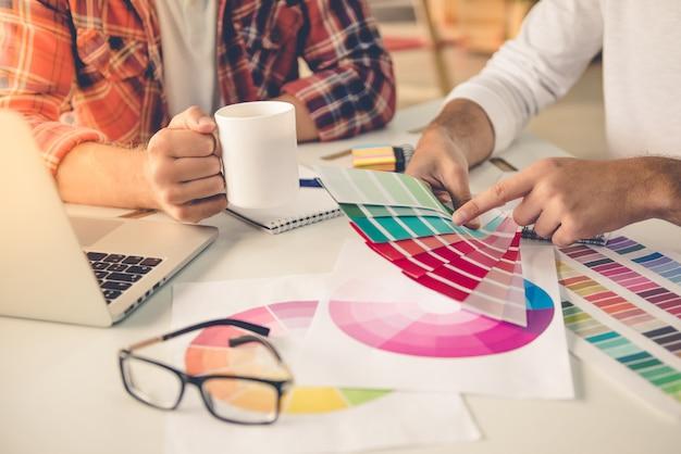 Designers em roupas casuais, discutindo as cores.