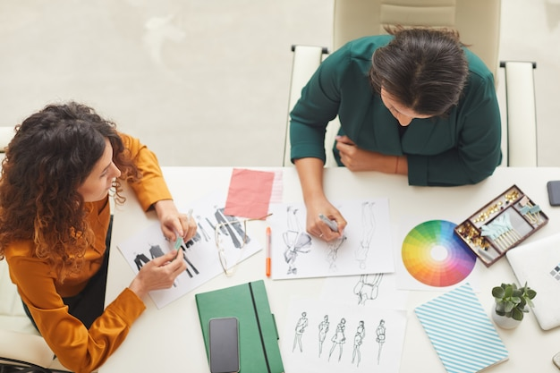 Designers fazendo roupas esboços tiro superior