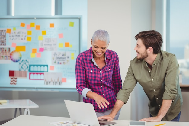 Designers gráficos discutindo no laptop
