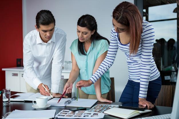 Designers gráficos discutindo sobre fotografias