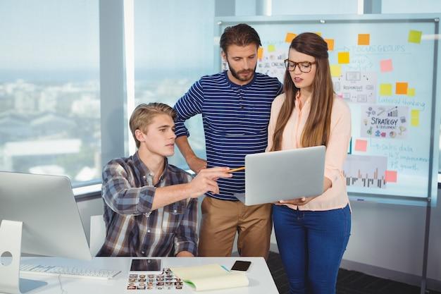 Designers gráficos discutindo sobre laptop