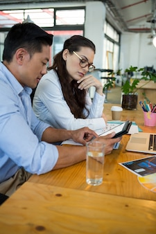 Designers gráficos discutindo sobre tablet digital