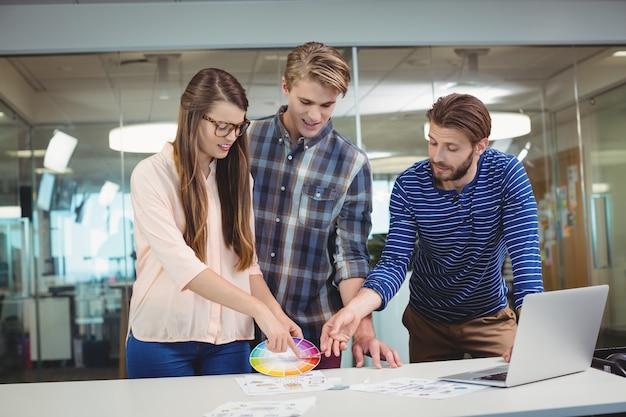 Designers gráficos interagindo uns com os outros enquanto trabalham