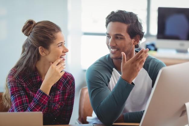 Designers gráficos masculinos e femininos interagindo uns com os outros na mesa