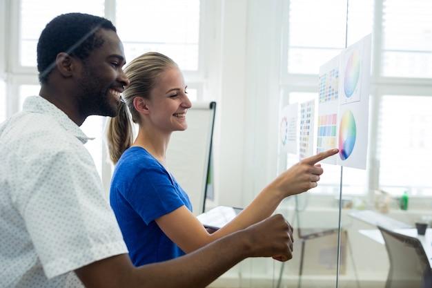 Designers gráficos masculinos e femininos que interagem sobre a carta de cor