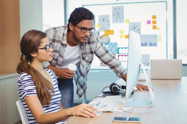 Designers gráficos masculinos e femininos trabalhando em uma sala de conferências
