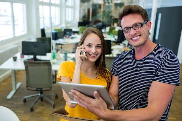 Designers gráficos masculinos e femininos usando a tabuleta digital