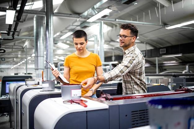 Designers gráficos profissionais controlando o processo da máquina de impressão moderna