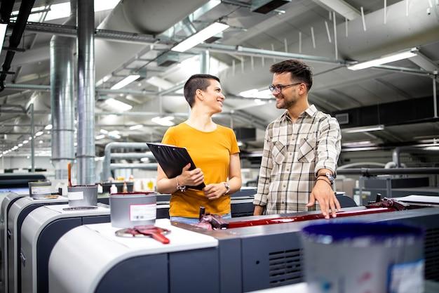 Designers gráficos profissionais verificando os valores de cor da máquina de impressão moderna