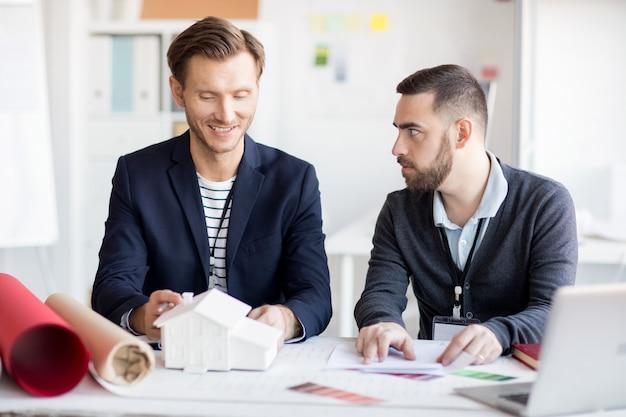 Designers masculinos discutindo casa