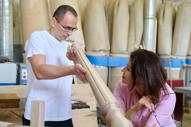 Designers masculinos e femininos, carpinteiros, engenheiros trabalhando em uma oficina industrial.