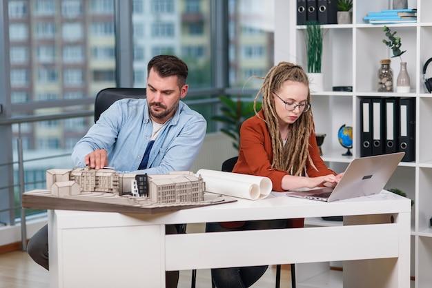 Designers masculinos e femininos criativos e qualificados, trabalhando com maquete de edifícios e plantas no laptop.