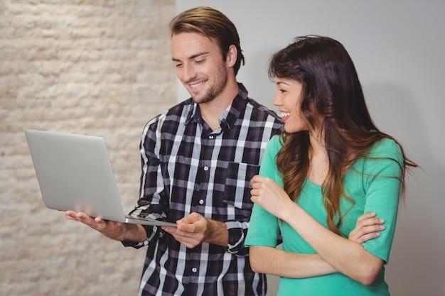 Designers masculinos e gráficos discutindo no laptop