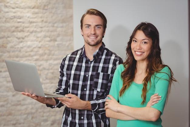 Designers masculinos e gráficos segurando um laptop