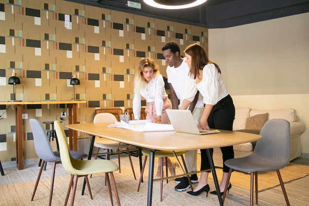 Designers multiétnicos de conteúdo em pé e olhando para o rascunho