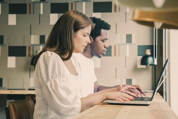 Designers multiétnicos sentados juntos e trabalhando em laptops em um espaço de coworking