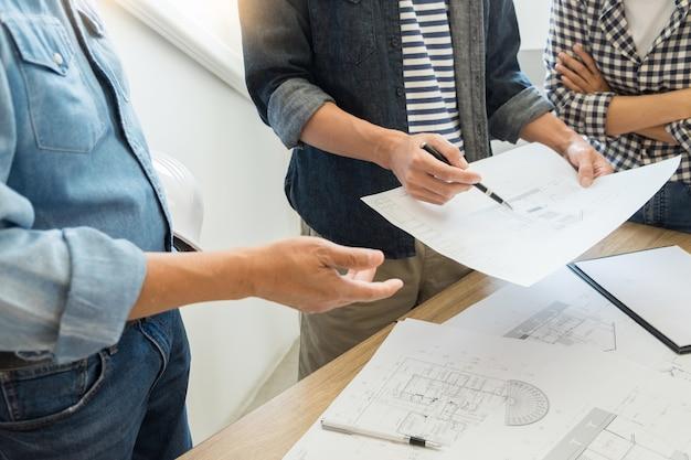 Designers no escritório estão trabalhando no discussion blueprint architect em um novo projeto