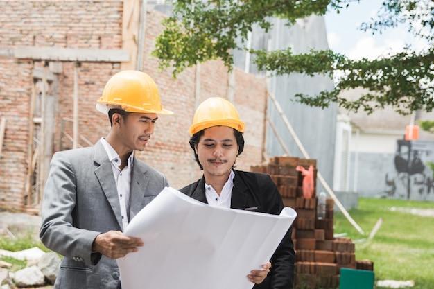 Designers que discutem o plano de construção de casa