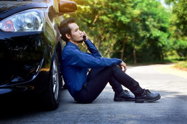 Desiludido homem segurando o telefone inteligente e sentado no carro estacionado na estrada
