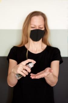 Desinfecção das mãos para proteger o coronavírus com desinfetante em spray durante a quarentena.