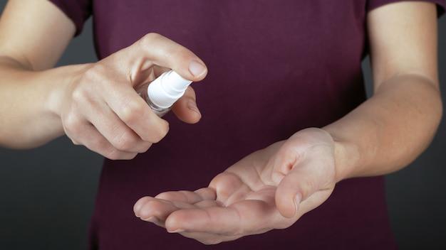 Desinfecção de close-up de mãos sobre um fundo escuro, conceito de saúde, higiene, proteção de micróbios, aplique spray anti-séptico