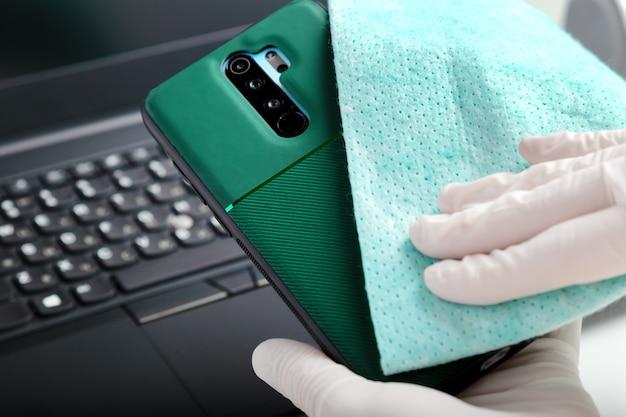 Desinfecção do teclado do telefone e laptop com álcool desinfetante. mulher de luvas limpa o telefone com tecido e desinfetante durante o período 19. proteção, higiene, prevenção de infecções, germes, bactérias