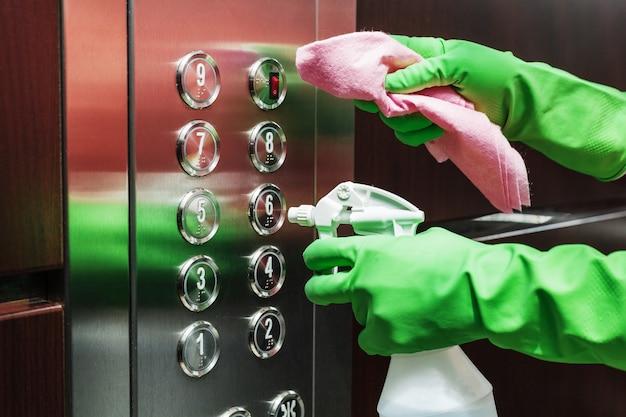 Desinfecção e cuidados higiênicos com álcool spray no botão do elevador.