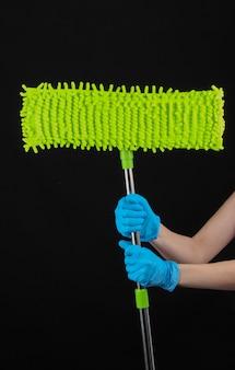 Desinfecção e limpeza da casa durante o período covid-19. mulher com as mãos nas luvas segura um esfregão na parede preta.