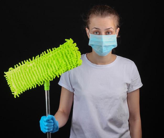 Desinfecção e limpeza da casa durante o período covid-19. mulher com uma máscara protetora médica, luvas segura um esfregão em uma parede preta.